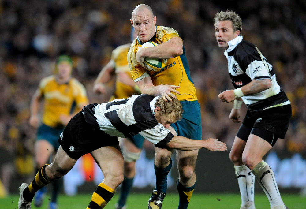 Australia's Stirling Mortlock (c) is tackled by Josh Lewsey (l) of the Barbarians