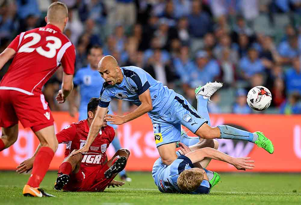 Adrian Mierzejewski of Sydney FC trips over Matt Simon of Adelaide United