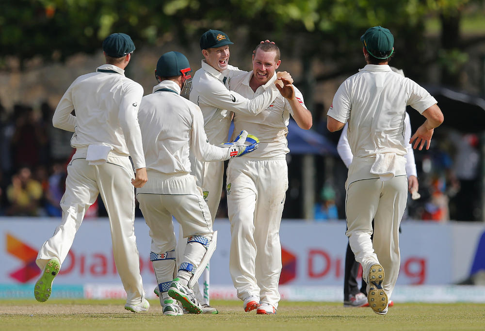 Jon Holland celebrates a wicket for Australia