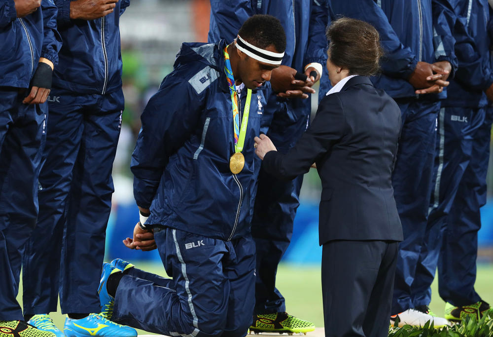Fijian players kneel while receiving their gold medals