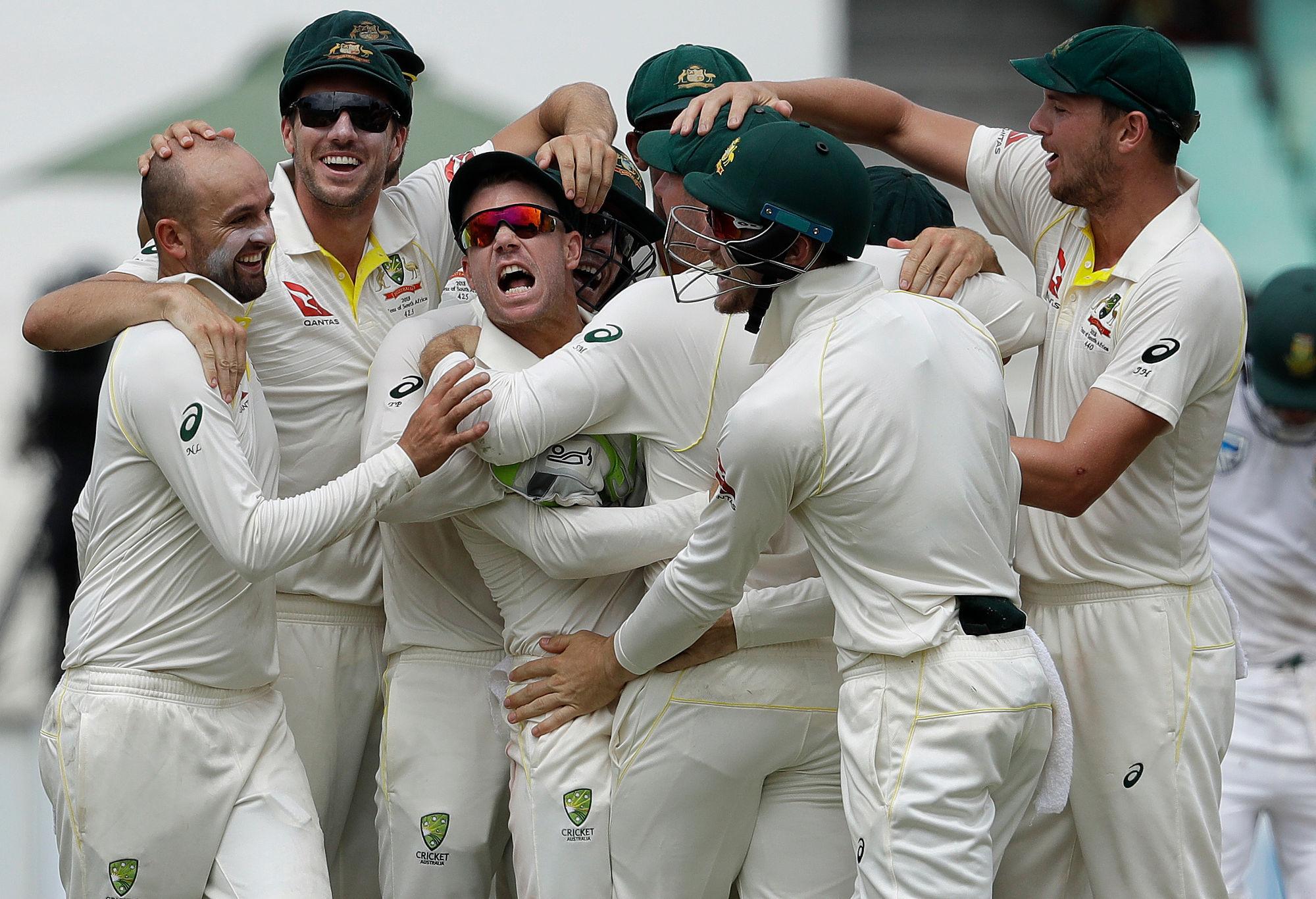 Australia's bowler Nathan Lyon, left, and teammates celebrate