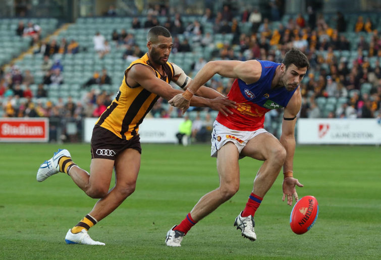 Michael Close of the Lions is pressured by Josh Gibson of the Hawks during the round eight AFL match between the Hawthorn Hawks and the Brisbane Lions at University of Tasmania Stadium on May 13, 2017 in Launceston, Australia.
