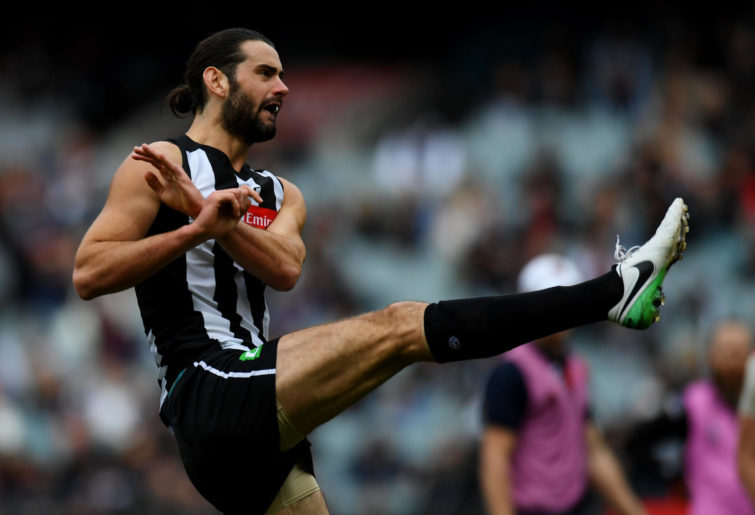 Brodie Grundy kicks the football