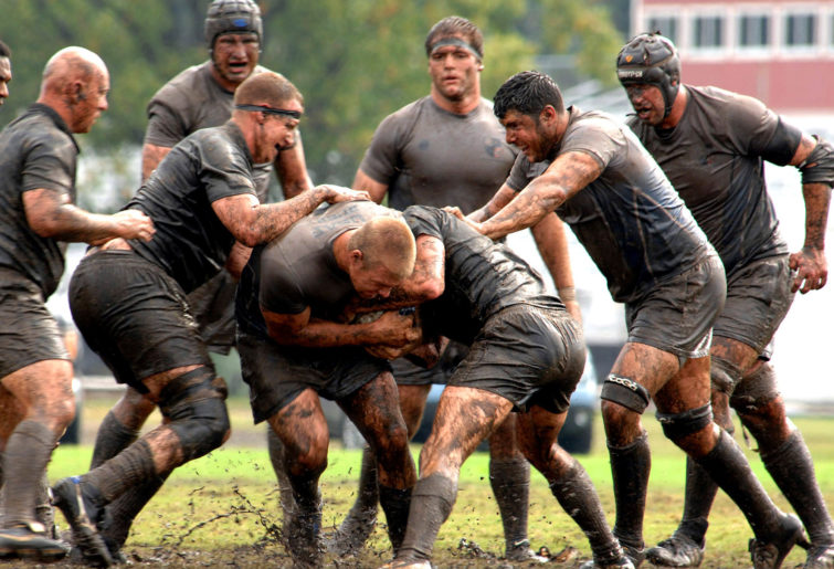 amateur rugby players in the mud