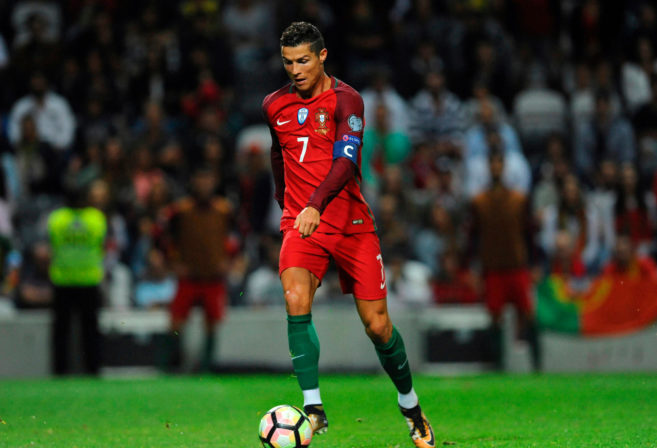 Portugal's Cristiano Ronaldo scores his side's fourth goal during the World Cup Group B qualifying soccer match between Portugal and Faroe Islands at the Bessa Stadium in Porto, Portugal.
