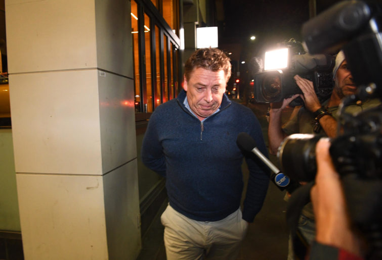 Mark Thompson is seen exiting the Melbourne Magistrates Court.