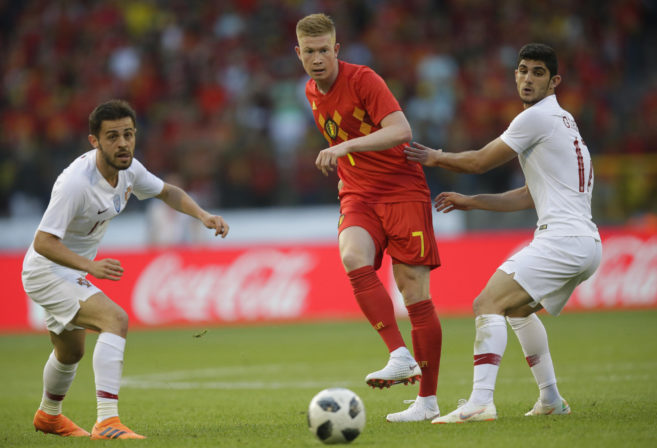Kevin de Bruyne kicks the ball through the Portugal defence.