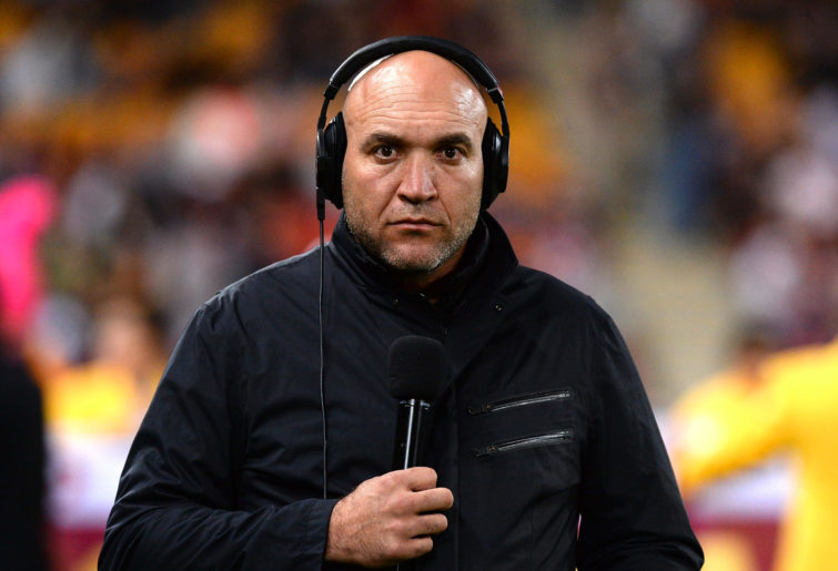 Gorden Tallis stands on the sidelines in commentary gear.