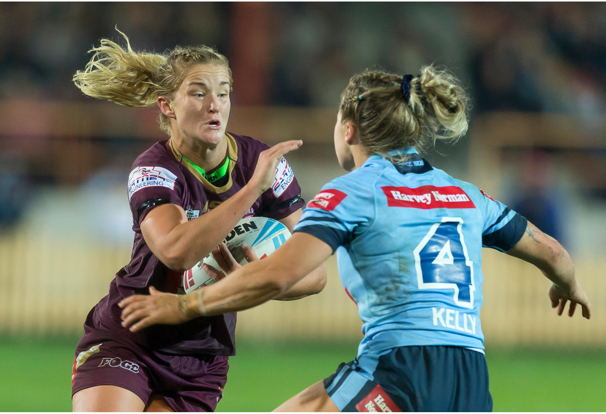 Meg Ward of the Maroons is tackled by Isabelle Kelly of the Blues.