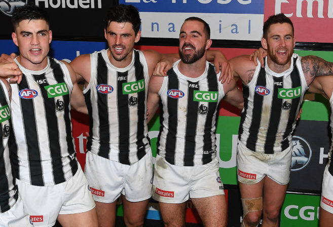 Collingwood Magpies players sing the team song after a victory