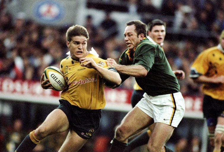 Tim Horan of Australia is tackled by Brendan Venter
