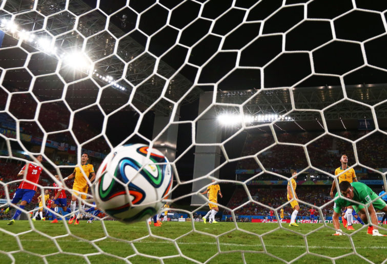 Ball hits the back of the net as Chile score against Australia.