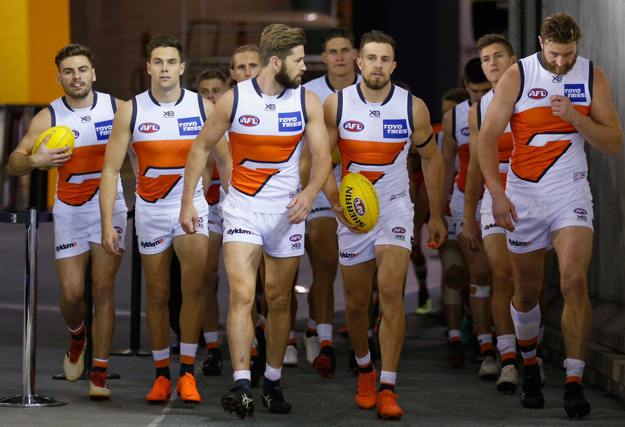 GWS Giants players run out of the tunnel.