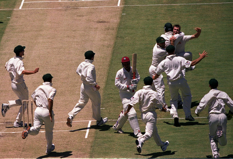 Glenn McGrath is mobbed by teammates after taking the wicket of Jimmy Adams to secure a hat-trick.