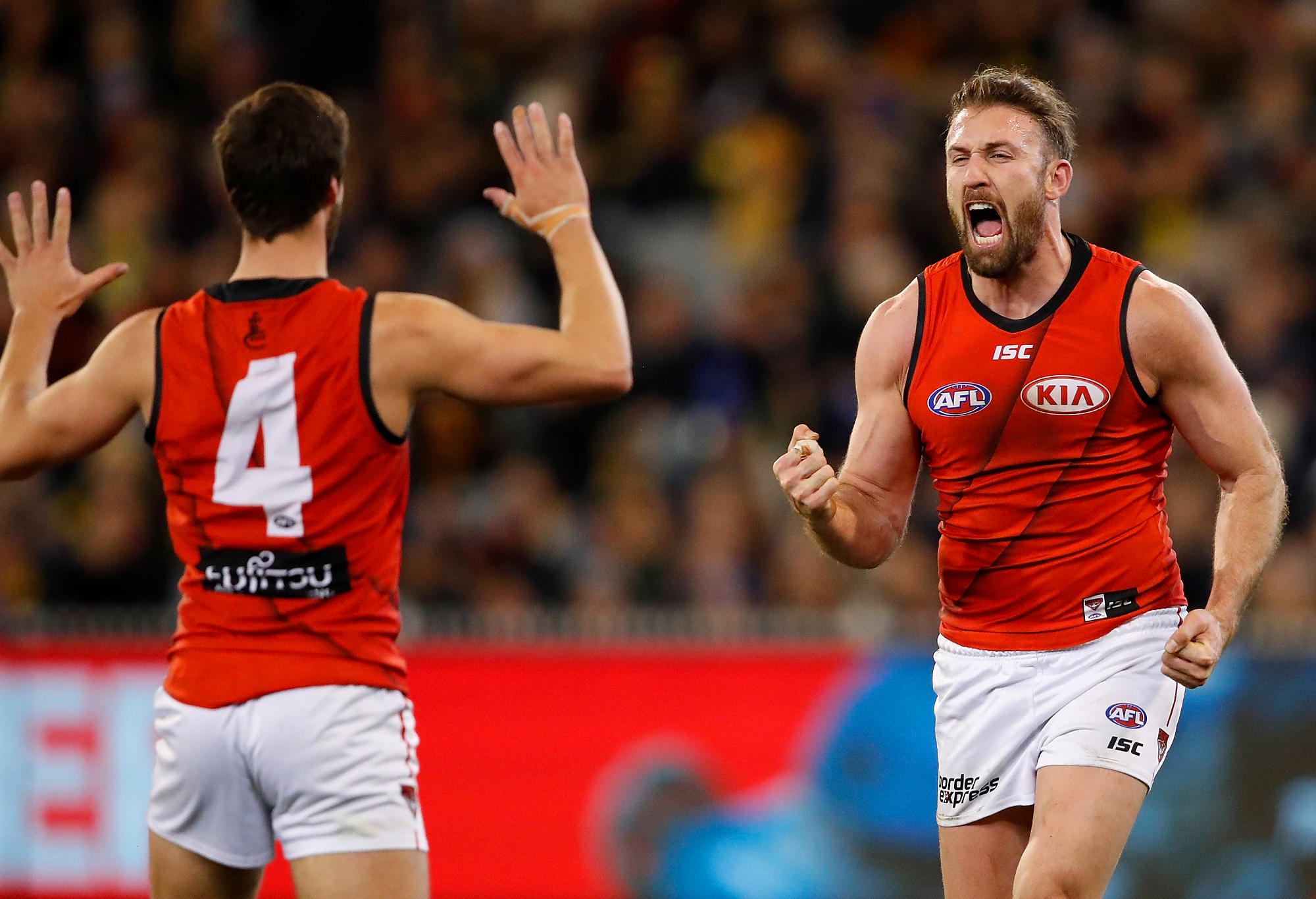Cale Hooker of the Bombers (R) celebrates a goal with Kyle Langford of the Bombers during the 2018 AFL round 22 match between the Richmond Tigers and the Essendon Bombers at the Melbourne Cricket Ground on August 17, 2018 in Melbourne, Australia.