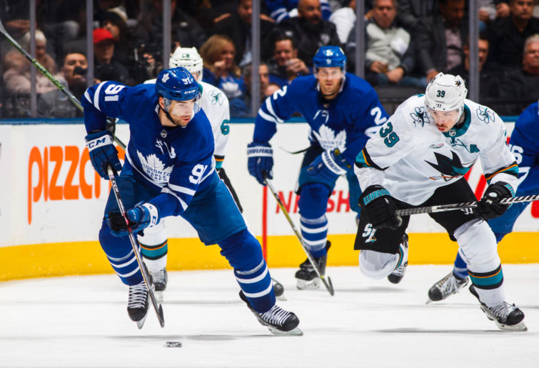 John Tavares of the Toronto Maple Leafs races Logan Couture of the San Jose Sharks for the puck.