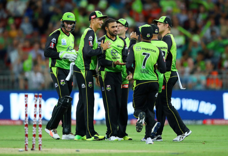 Members of the Sydney Thunder team celebrate a wicket.