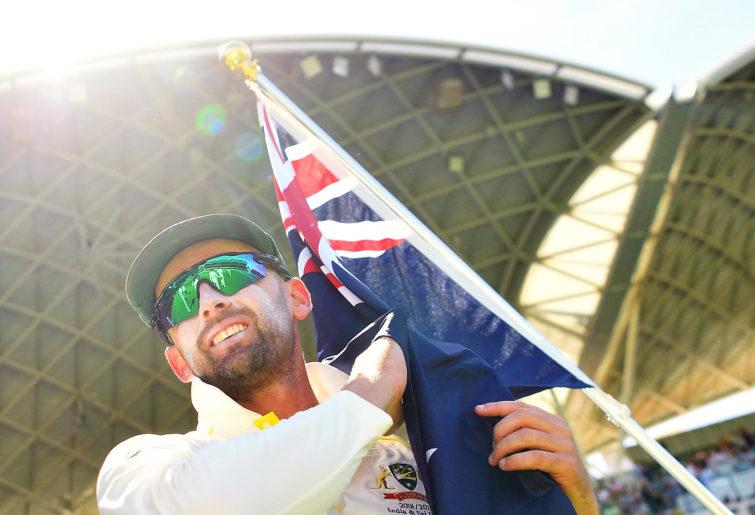 Nathan Lyon of Australia walks onto the ground with the Australian flag