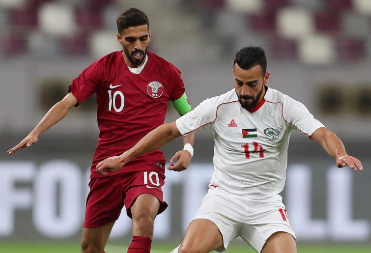 Qatar's Hasan al-Haydos vies for the ball against Palestine's Abdala Jaber