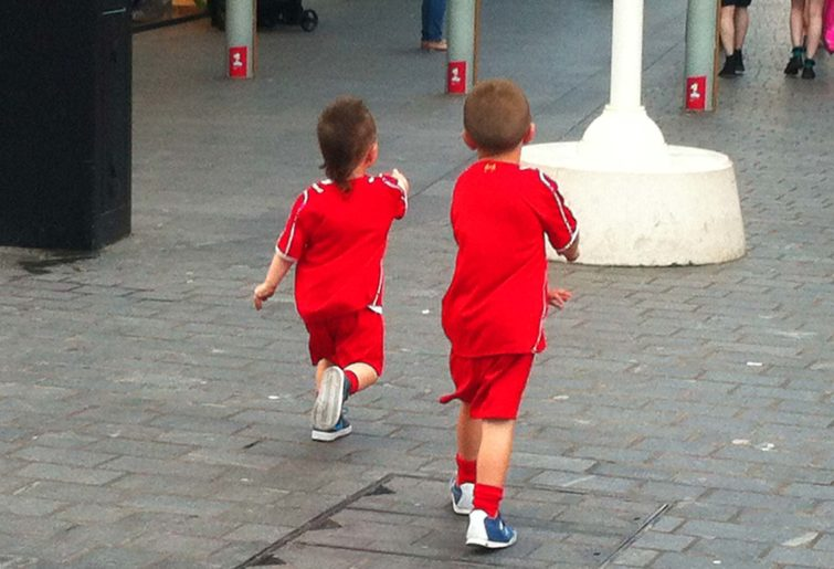 Two kids wearing Liverpool FC kits