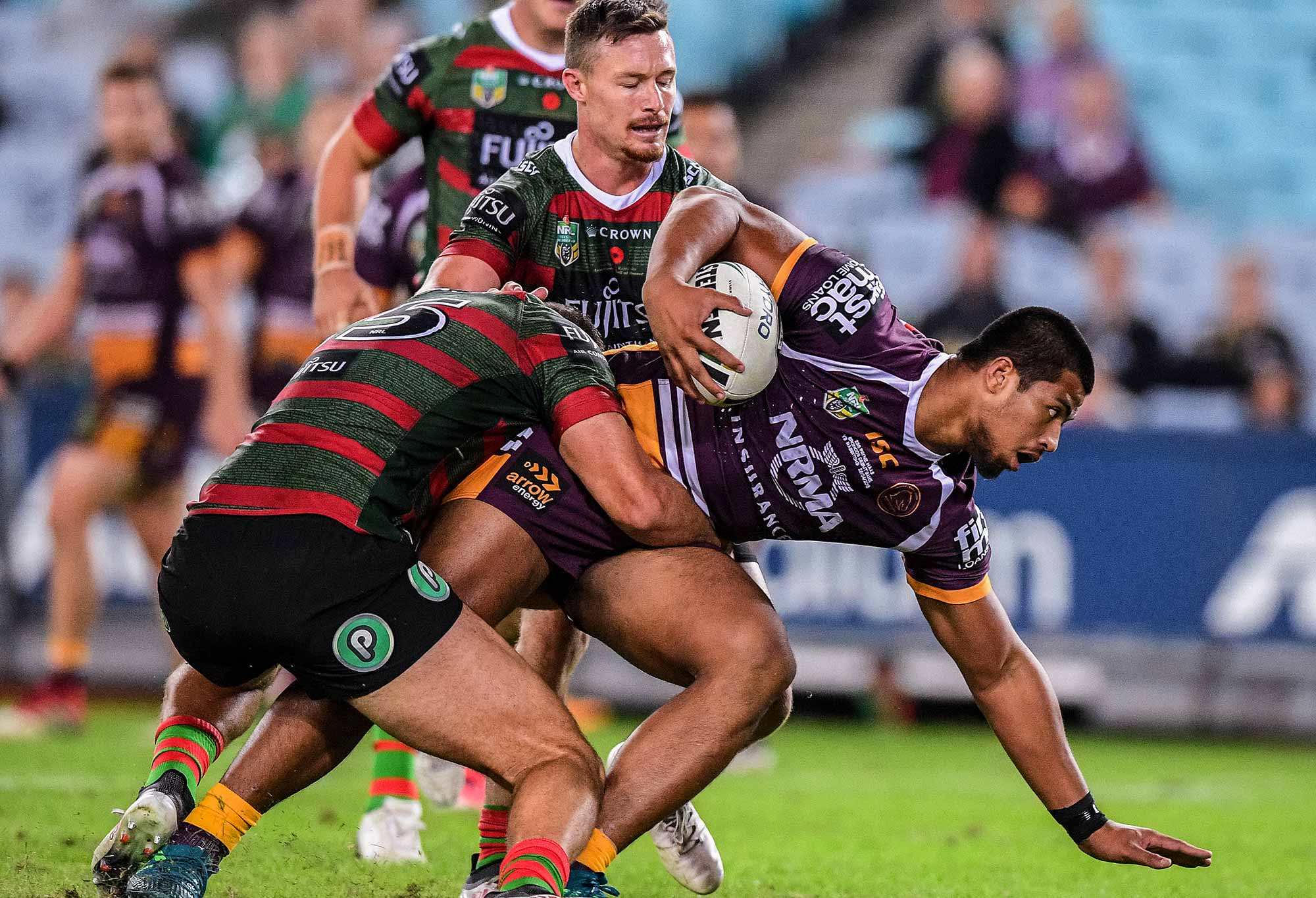 Payne Haas (right) of the Broncos is tackled by Robert Jennings of the Rabbitohs