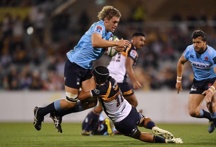Ned Hanigan of the Waratahs (centre) is tackled by Christian Lealiifano of the Brumbies.