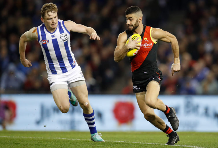 North Melbourne's Jack Ziebell chases Essendon's Adam Saad
