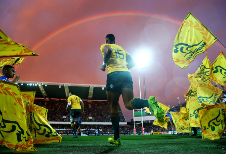 Israel Folau runs onto the field underneath a rainbow