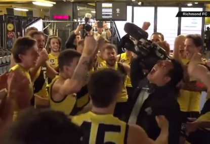 Cheeky moment ensues as camera man mobbed by Richmond VFL team post-song