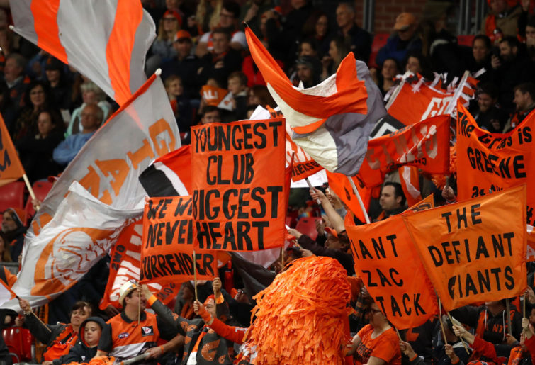 GWS Giants fans cheer at an AFL match.