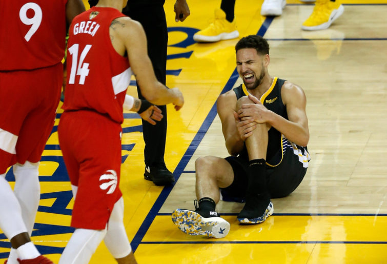 Klay Thompson lies injured on the court.