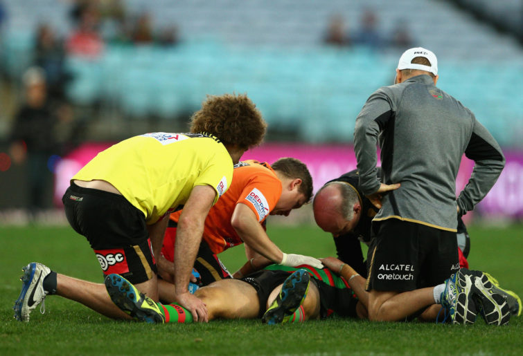 Kyle Turner of the Rabbitohs is assisted from the field after a concussion