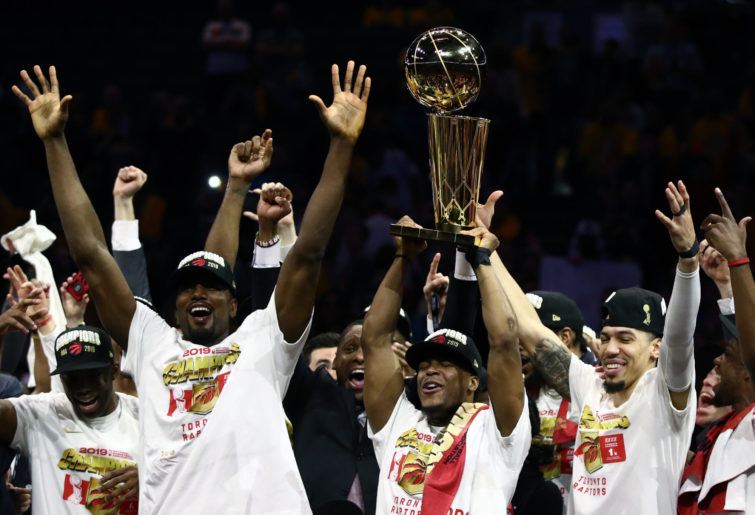 Toronto Raptors players celebrate with the Larry O'Brien trophy.