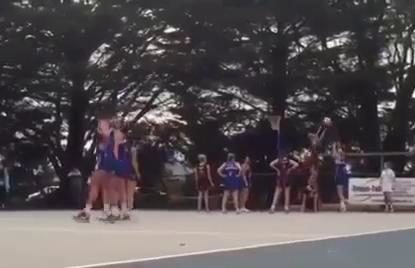 Netball player blocks shot by standing on teammate