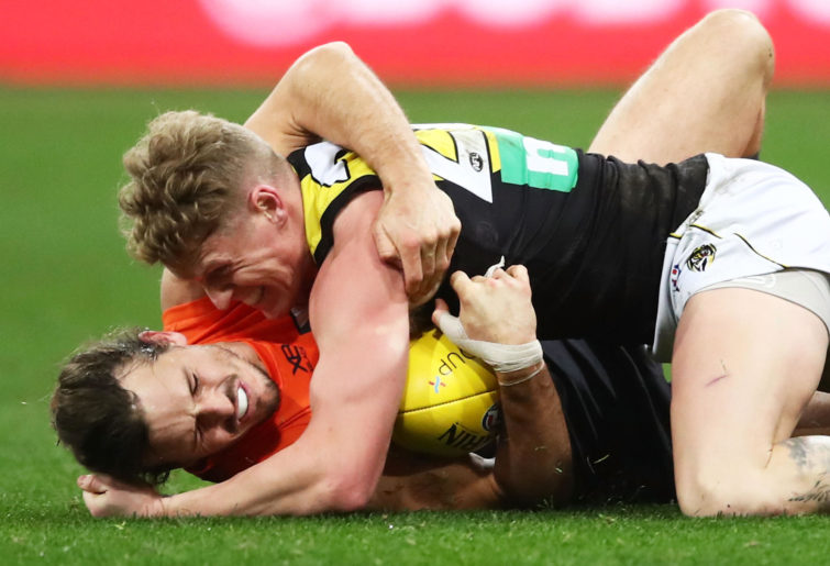 Phil Davis of the Giants competes for the ball against Josh Caddy of the Tigers