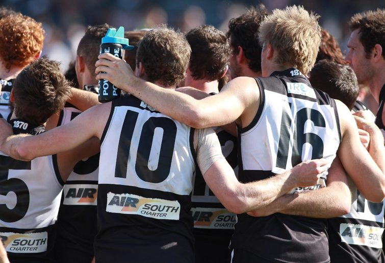 Port Adelaide Magpies players huddle.