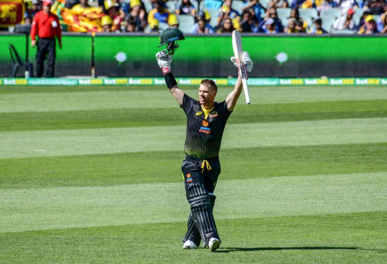 Australian batsman David Warner celebrates his first 100 runs