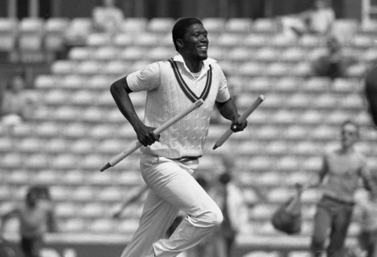 Joel Garner runs with a wicket stump in each hand.