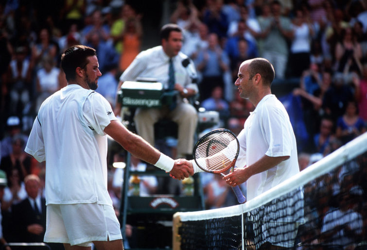Patrick Rafter of Australia shakes hands with Andre Agassi