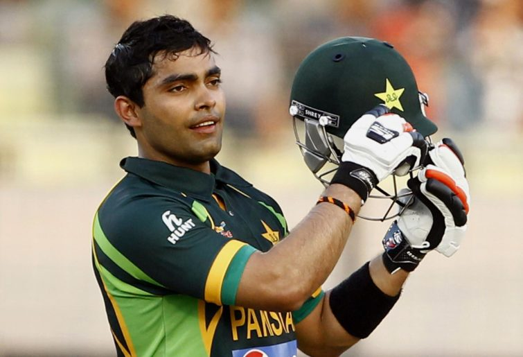 Umar Akmal takes off his helmet.