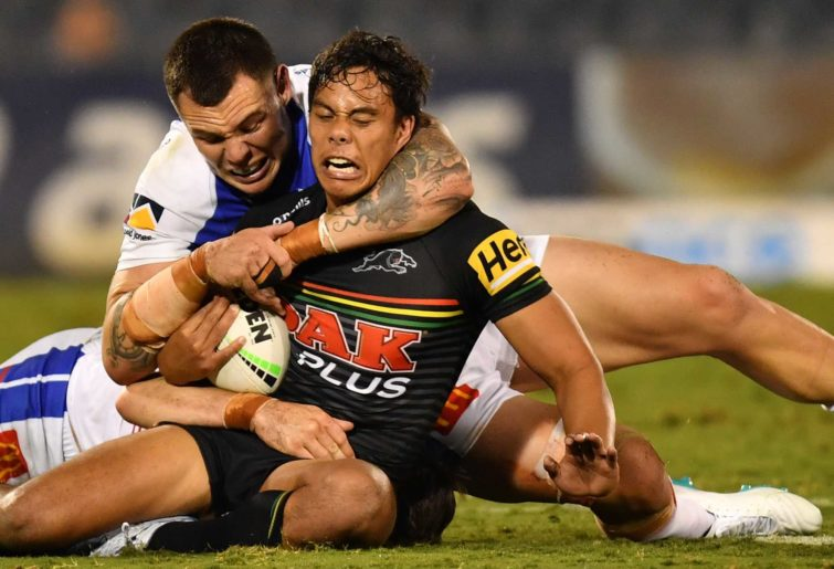Jarome Luai of the Panthers is tackled by David Klemmer and Aidan Guerra of the Knights