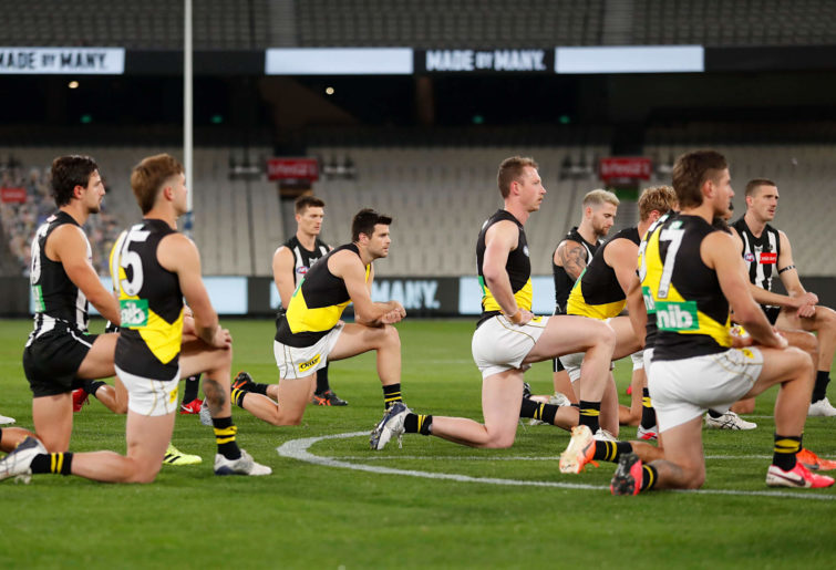 Collingwood and Richmond players take a knee to support the Black Lives Matter movement