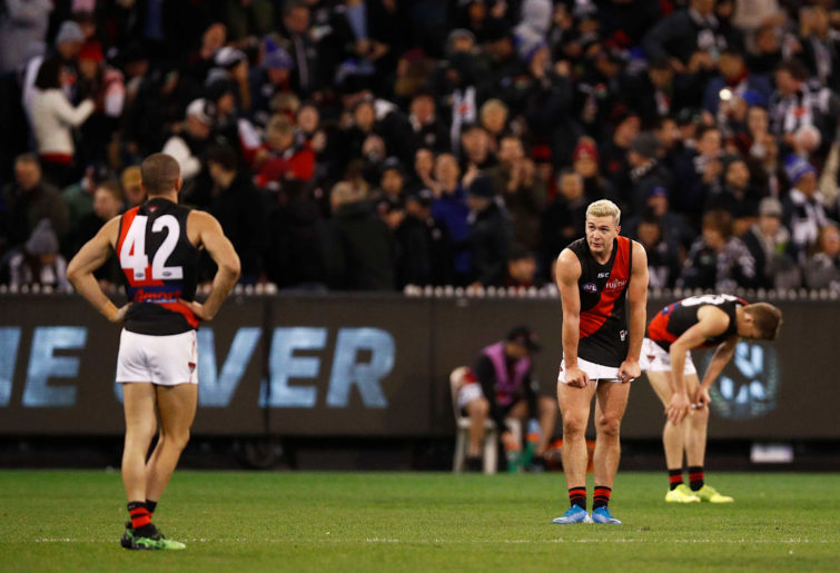 Conor McKenna and other Bombers players look dejected