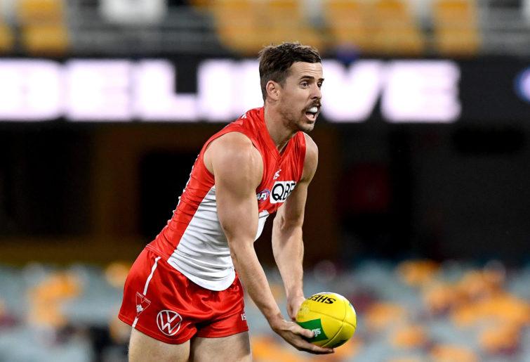 Jake Lloyd of the Swans handballs