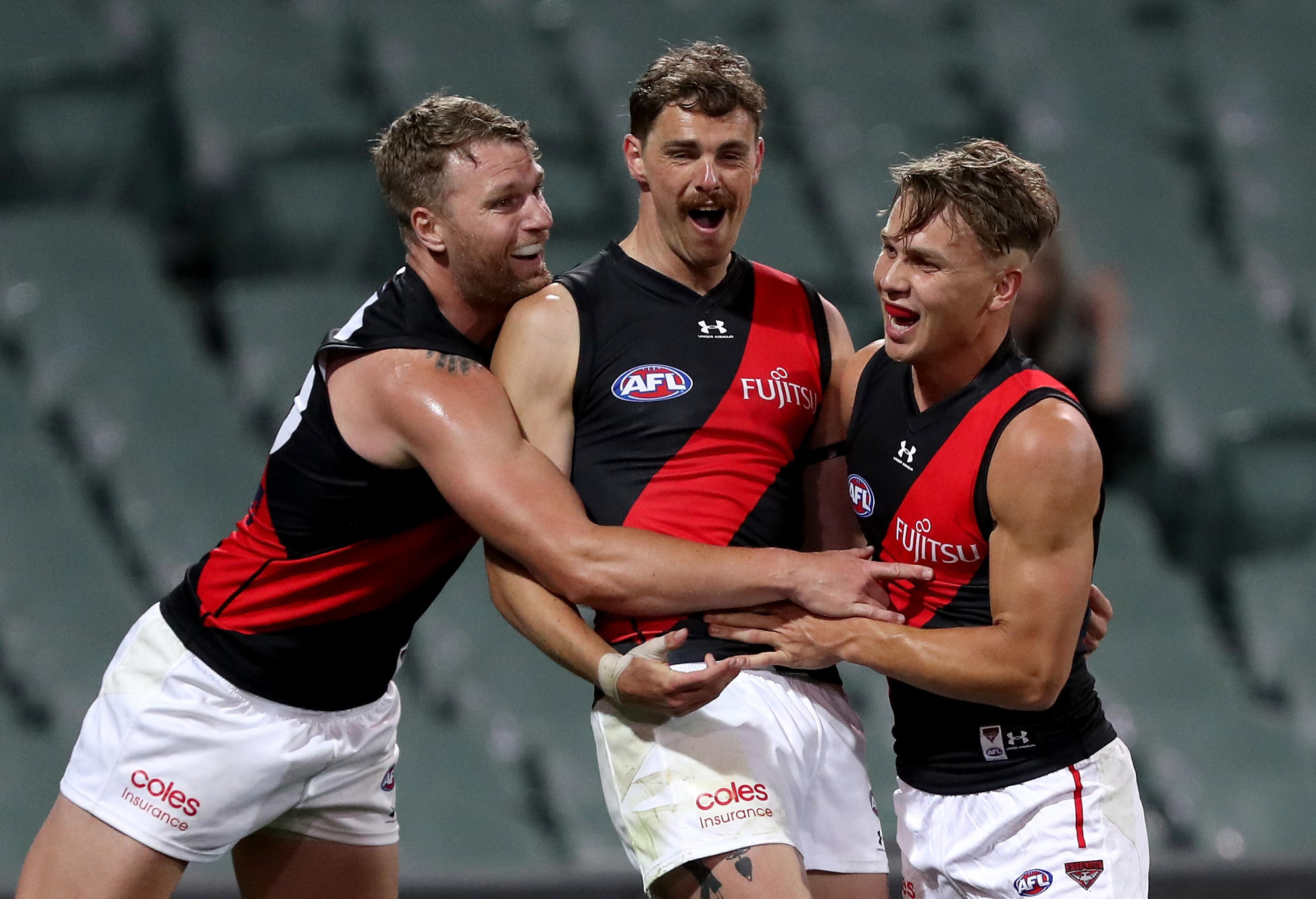 Jake Stringer, Joe Daniher and Jackson Ross of the Bombers celebrate a goal