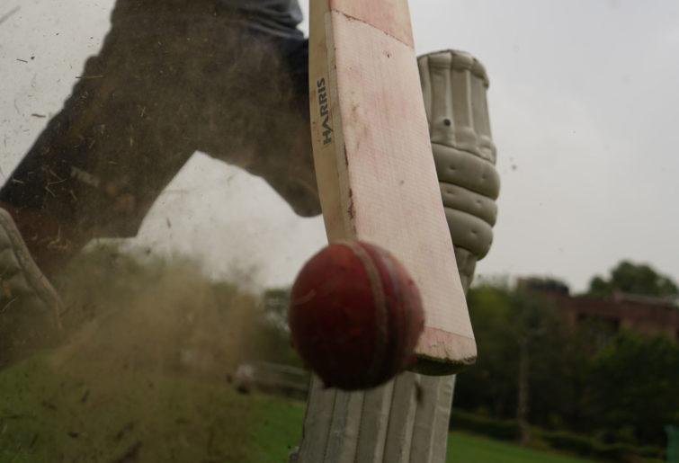 A cricket ball coming off a bat