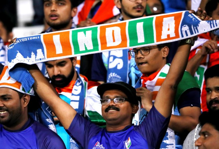 An Indian football fan holds aloft a scarf with the word 'INDIA' printed on it.