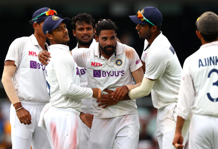 India's paceman Mohammed Siraj (C) celebrates his fifth wicket with teammates