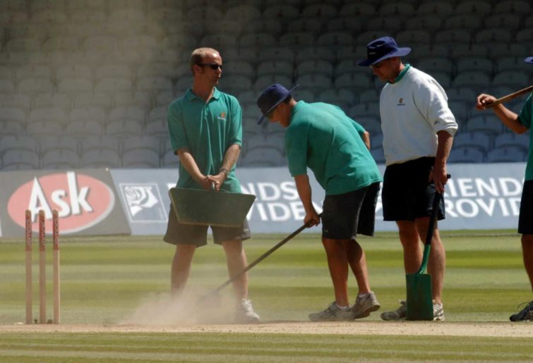 Groundstaff tend to a dry pitch