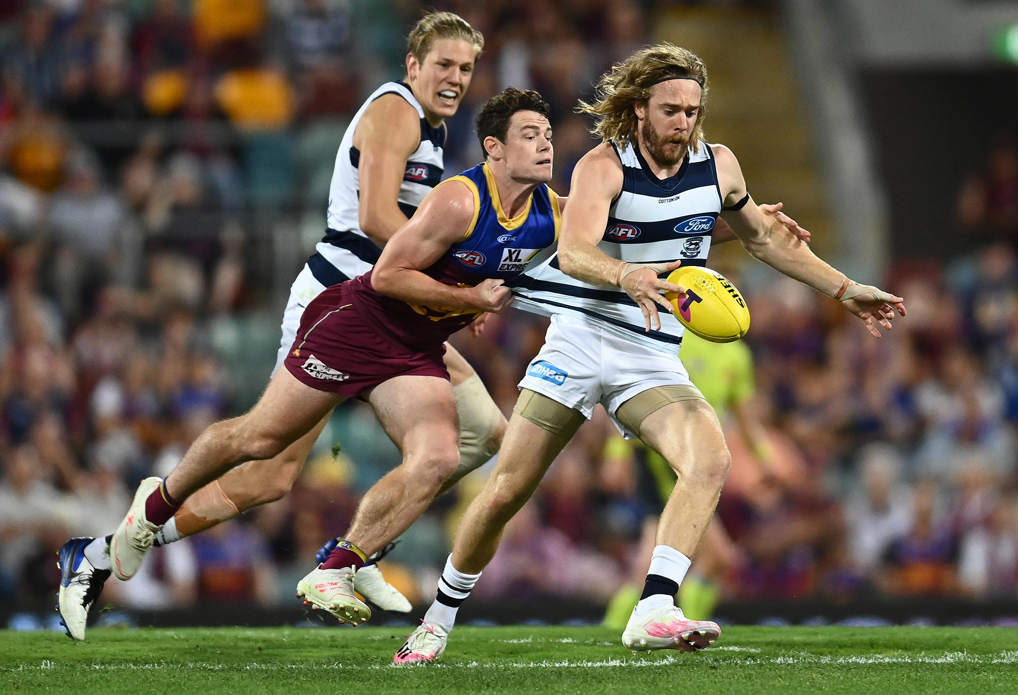 Cameron Guthrie of the Cats is challenged by Lachie Neale of the Lions